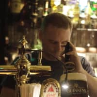 Here's to friends: John Coyle pours a beer at his pub What The Dickens!, a part of the international community for 25 years.