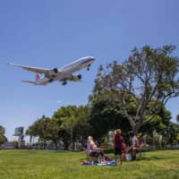 A family watches a China Airlines plane landing at Los Angeles International Airport at the start of the Memorial Day holiday weekend on Friday. | AFP-JIJI