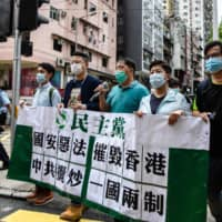 Pro-democracy protesters hold a banner that translates as 'Vicious national security law destroys Hong Kong; Chinese Communists seek mutual destruction of one country two systems' as they march in Hong Kong on Friday. | AFP-JIJI