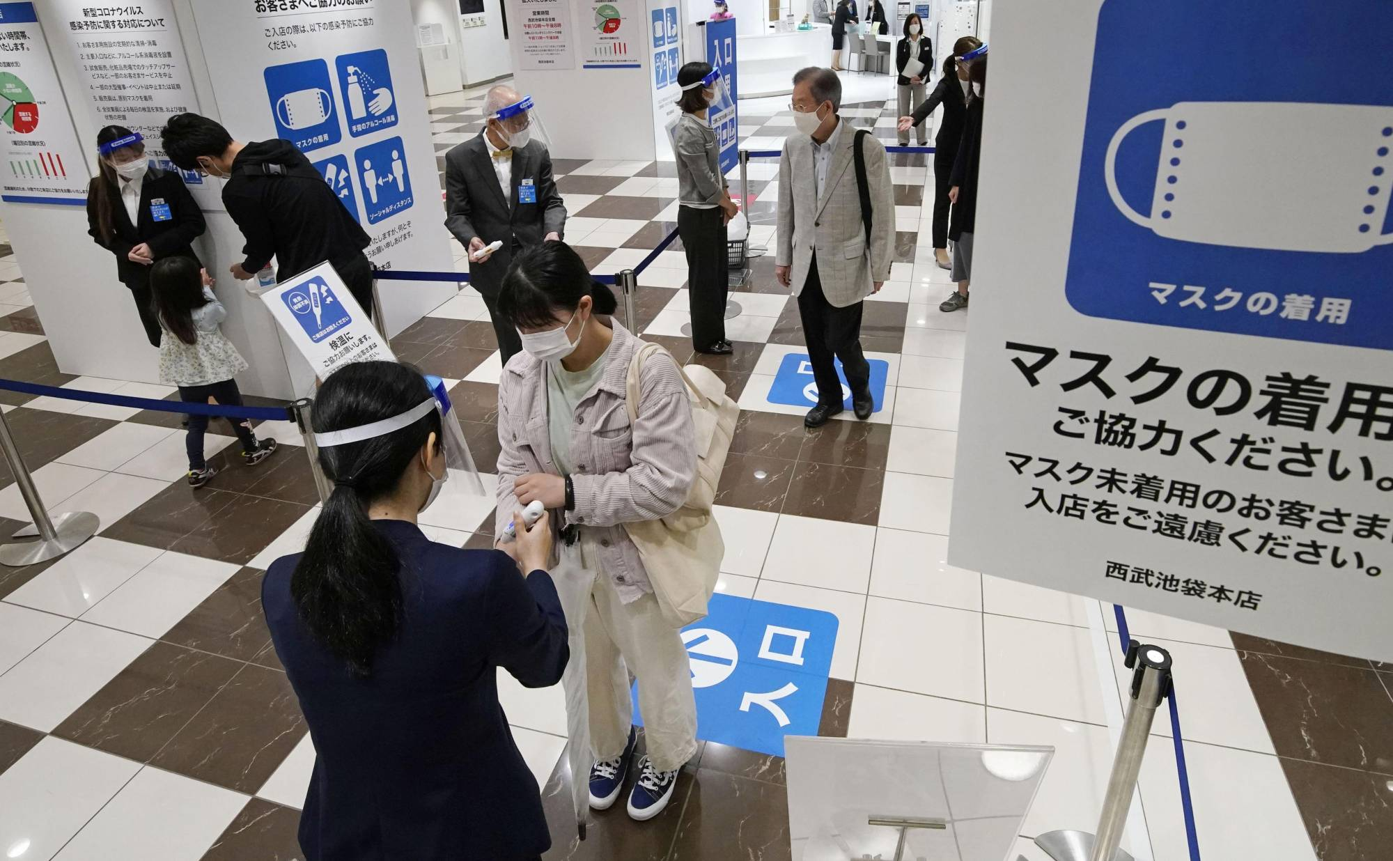 Customers have their temperatures checked at an entrance of the Seibu department store in Tokyo's Ikebukuro district on Saturday.  | KYODO