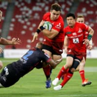 The Sunwolves' Gerhard van den Heever tries to avoid a tackle during a Super Rugby match on Feb. 23 in Singapore. | REUTERS