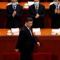 Chinese President Xi Jinping walks past officials wearing face masks as he arrives for the opening session of the National People's Congress at the Great Hall of the People in Beijing on Friday. | REUTERS