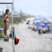 A lifeguard looks out from a stand at Kure Beach, North Carolina, on Saturday. The town lifted the majority of beach restrictions related to the coronavirus on May 15.    THE STAR-NEWS / VIA AP