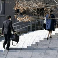 College students wearing masks walk to a job fair in Tokyo's Minato Ward on March 1, as the year's job-hunting season officially began amid spreading coronavirus infections. | KYODO