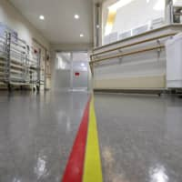 Red and yellow tapes to create zones are seen on a corridor of a hospital in the city of Osaka assigned to exclusively treat coronavirus patients with moderate symptoms in a photo taken on May 16. | KYODO