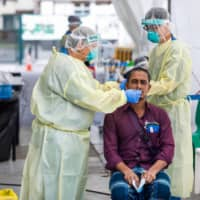 Medical staff test a migrant worker at the Avery Lodge for COVID-19 in Singapore on May 15. | SINGAPORE MINISTRY OF MANPOWER / VIA AFP-JIJI