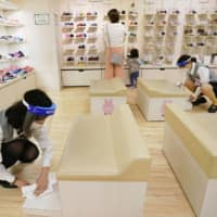 Staff disinfect an area selling children's items at Seibu Department Store in Tokyo's Ikebukuro district on Saturday, the day it reopened. | KYODO