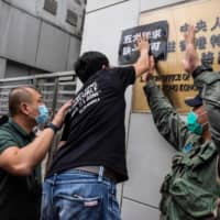 A pro-democracy activist places a placard on a wall during a protest outside the Chinese Liaison Office in Hong Kong on Sunday.  | AFP-JIJI