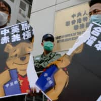 Members of the Neo Democrats party hold a torn placard depicting Winnie the Pooh, a reference to Chinese President Xi Jinping, outside the Chinese Liaison Office in Hong Kong on Sunday.  | BLOOMBERG