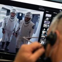 This handout photo released by NASA shows NASA astronauts Robert Behnken, left, and Douglas Hurley, right,  taking part in a dress rehearsal Saturday in preparation for the launch of a SpaceX Falcon 9 rocket. | JOEL KOWSKY / NASA / VIA AFP-JIJI
