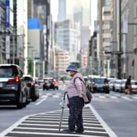 An elderly woman crosses a street in Tokyo on Sunday. On Monday, the government plans to lift the state of emergency imposed on the Tokyo metropolitan area and Hokkaido, according to government sources.   AFP-JIJI