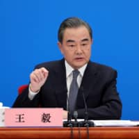 Chinese Foreign Minister Wang Yi speaks to reporters via video link at a news conference held on the sidelines of the National People's Congress at the Great Hall of the People in Beijing on Sunday.  | CHINA DAILY / VIA REUTERS