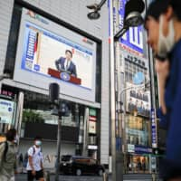 A large screen on a building shows a live broadcasting of Prime Minister Shinzo Abe's news conference on Japan's response to the coronavirus outbreak in Tokyo's Shinjuku district on May 14. Japan's coronavirus state of emergency was coming to an end, but Abe's political troubles may be just beginning. | REUTERS