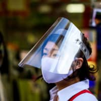 A shop worker in Tokyo's Sugamo district is doubly protected with a facial mask and screen.  | AFP-JIJI