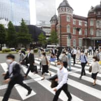 Commuters cross a street outside Tokyo Station on Monday morning, hours before the government officially lifted the state of emergency in the remaining five prefectures including the capital — setting the stage for the entire country to enter the next phase in its battle against the novel coronavirus. | KYODO