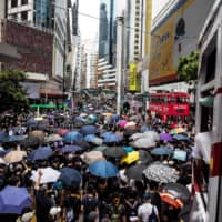 Pro-democracy protesters gather in the Causeway Bay district of Hong Kong on Sunday ahead of planned protests against a proposal to enact new security legislation in Hong Kong. The legislation is expected to ban treason, subversion and sedition, and follows repeated warnings from Beijing that it will no longer tolerate dissent in Hong Kong. | AFP-JIJI