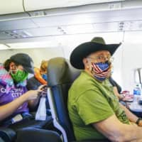 Passengers wear masks on an American Airlines flight in California on Wednesday. From June, Japan's ANA will require passengers to wear masks inside airports and aboard aircraft. | GETTY IMAGES / VIA KYODO