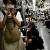 Commuters ride a train in Tokyo on Monday. | AFP-JIJI