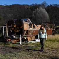 Anita Lawrence stands in front of a charred bus near to where she lives with her five children in a makeshift shelter months on from the devastating bush fires in Bemboka, a town on the south coast of New South Wales, Australia, last week.   AFP-JIJI
