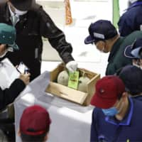 A pair of melons farmed in Yubari, Hokkaido, are auctioned and sold for ¥120,000 on Monday in Sapporo.  | KYODO