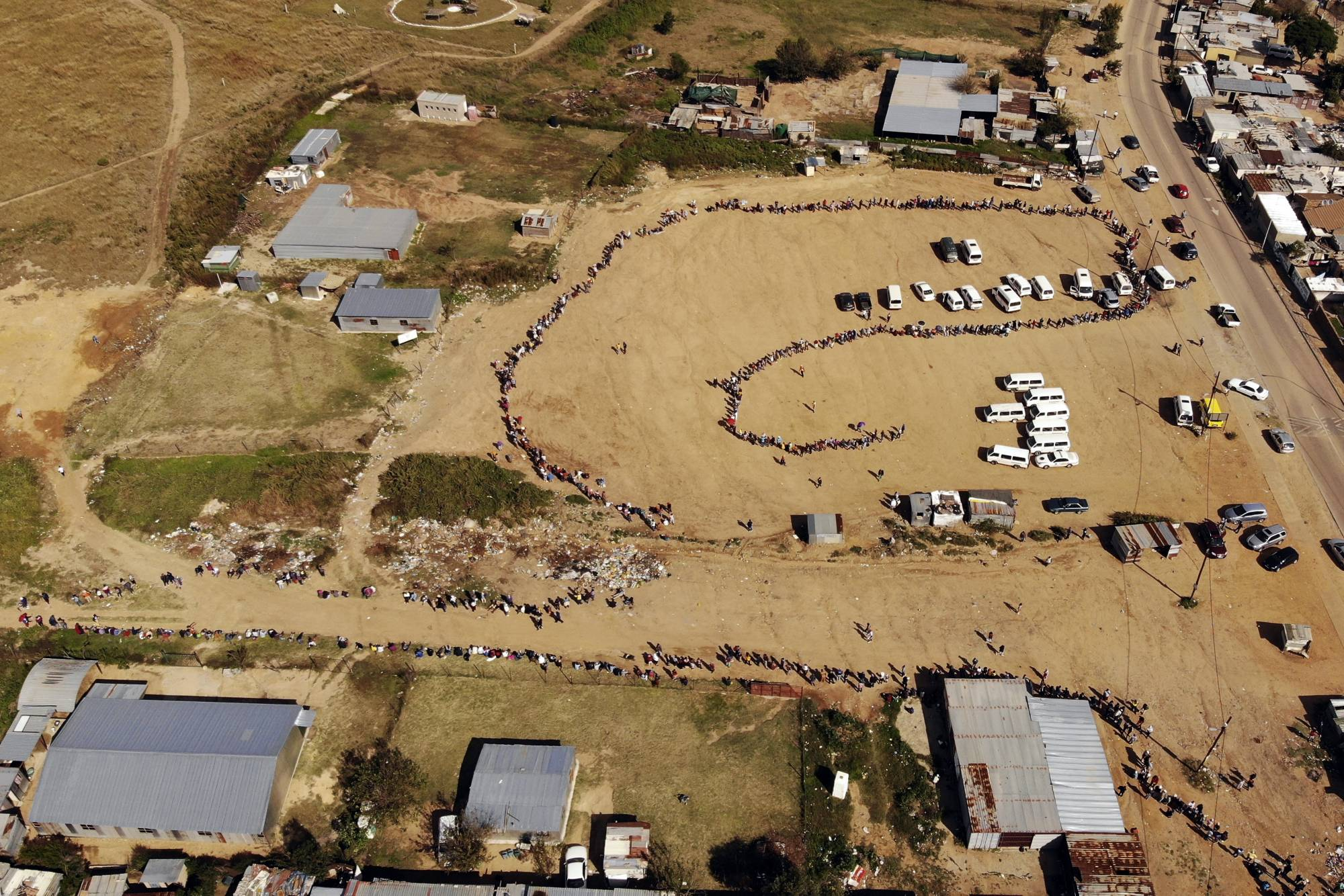 Thousands of people line up to receive food handouts in the Olievenhoutbos township of Midrand, South Africa. The country with the Africa's most developed economy also has its highest number of infections with more than 22,500. | AP