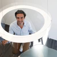 Designer Christophe Gernigon poses with a prototype of Plex'Eat, a plexiglass bubble that he designed to  protect diners from the novel coronavirus as restaurants in France prepare to re-open following a long lockdown. | REUTERS