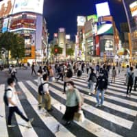 People walk at the famed scramble crossing in Tokyo's Shibuya district on Monday night, shortly after Prime Minister Shinzo Abe announced the end of the state of emergency. | KYODO