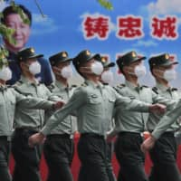 Chinese People's Liberation Army soldiers  march past a banner depicting Chinese President Xi Jinping inside the Tiananmen Gate in Beijing during a plenary session of China's National People's Congress at the Great Hall of the People on Monday. | AP