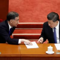 Chinese President Xi Jinping and Wang Yang, chairman of the National Committee of the Chinese People's Political Consultative Conference, speak at the second plenary session of the National People's Congress at the Great Hall of the People in Beijing on Monday.  | REUTERS