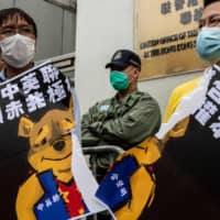 Pro-democracy activists tear a placard of Winnie-the-Pooh, representing Chinese President Xi Jinping, during a protest against proposed new security laws outside the Chinese Liaison Office in Hong Kong on Sunday.  | AFP-JIJI