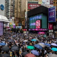Pro-democracy protesters gather in the Causeway Bay district of Hong Kong on Sunday.  | AFP-JIJI