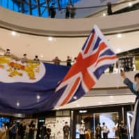 A demonstrator waves a colonial-era Hong Kong flag during a protest at the International Finance Center shopping mall in Hong Kong on Monday.  | BLOOMBERG