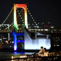 A couple embrace each other in Tokyo on Monday night with the Rainbow Bridge in the background, lit up in seven colors to commemorate the end of the state of emergency in Japan. | RYUSEI TAKAHASHI