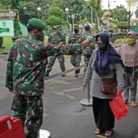 A soldier takes the temperature of a person while waiting in line at a rice distribution center at the Central Jakarta Military District Command on May 13. | BLOOMBERG