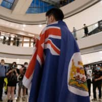A demonstrator wears a colonial-era Hong Kong flag during a protest against a planned national security law held in the International Finance Center shopping mall in Hong Kong on Monday.  | BLOOMBERG