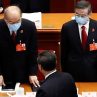 Chinese President Xi Jinping is seen with Zhang Jun, procurator-general of the Supreme People's Procuratorate, and Zhou Qiang, chief justice and president of the Supreme People's Court, as he leaves at the end of the second plenary session of the National People's Congress at the Great Hall of the People in Beijing on Monday. | REUTERS
