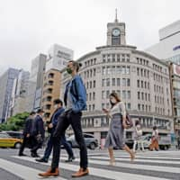 People walk in Tokyo's Ginza shopping district on Tuesday, a day after the state of emergency was lifted in Tokyo and four other prefectures.  | KYODO