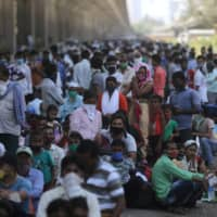 Migrants wait along a road for transportation to a railway station during an extended lockdown to slow the spread of the coronavirus in Mumbai on Friday.  | REUTERS