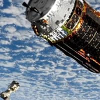 Japan's Kounotori 9 unmanned cargo spacecraft approaches the robot arm (below left) of the International Space Station. | NASA TV / VIA KYODO