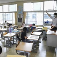 Pupils attend a class at an elementary school in Toyota, Aichi Prefecture, on Monday as the school reopens. Only half of the students are allowed to come each day to avoid crowding. | KYODO
