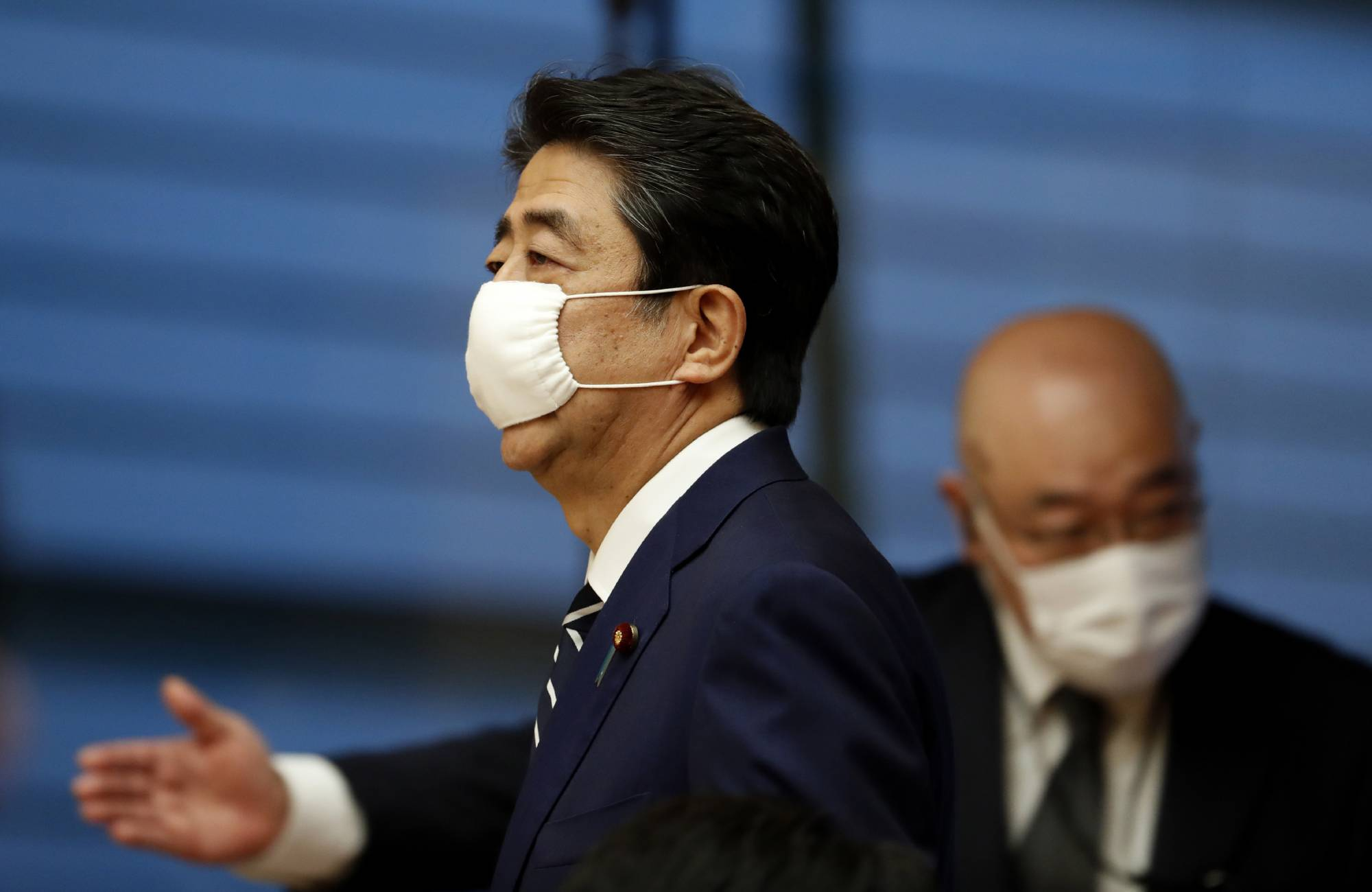 Prime Minister Shinzo Abe wears a protective mask ahead of a news conference in Tokyo on Monday. | POOL / VIA AP