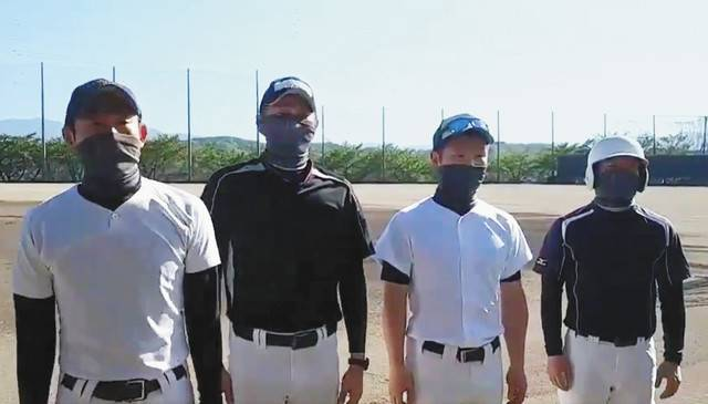 A screenshot from a video shows Shinji Takemine (left), a manager of a baseball team at Komoro Commercial High School in Komoro, Nagano Prefecture, and others wearing special antimicrobial masks. | SHINJI TAKEMINE / VIA CHUNICHI SHIMBUN