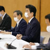 Prime Minister Shinzo Abe discusses the government's second extra budget at a meeting with the ruling parties on Wednesday morning in Tokyo. | KYODO
