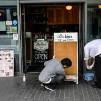 Employees prepare to reopen a restaurant in Tokyo on Tuesday, a day after the government lifted the COVID-19 state of emergency and started gradually reopening an economy that has plunged into a recession for the first time since 2015. | AFP-JIJI