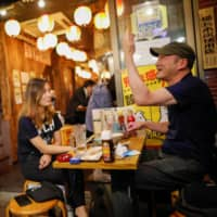 People enjoy drinks at a traditional Japanese-style pub in Tokyo's Ueno district on Tuesday, a day after the government lifted the state of emergency for the entire nation. | REUTERS