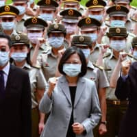 Taiwan President Tsai Ing-wen (center) poses for photographs with National Security Council Secretary-General Wellington Koo (left) and Defense Minister Yen Teh-fa while inspecting military police headquarters in Taipei on Tuesday. | AFP-JIJI