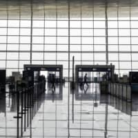 People walk through the near empty departure hall of the Wuhan Tianhe International Airport in Wuhan, China, on May 2. | BLOOMBERG