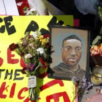 A portrait of George Floyd is seen as part of a memorial that was placed near the site of his arrest in Minneapolis.   AP