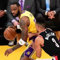 The Lakers' LeBron James (left) is defended by the Blazers' CJ McCollum during a game on Jan. 31 in Los Angeles.   AFP-JIJI