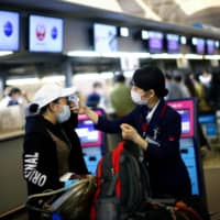 An employee of Japan Airlines scans the temperature of a passenger at the almost empty Kansai International Airport in Osaka on March 14. | REUTERS